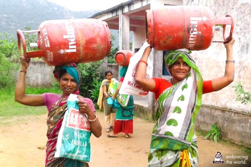 Indische Dorfbewohnerinnen mit Flüssiggas-Behältern