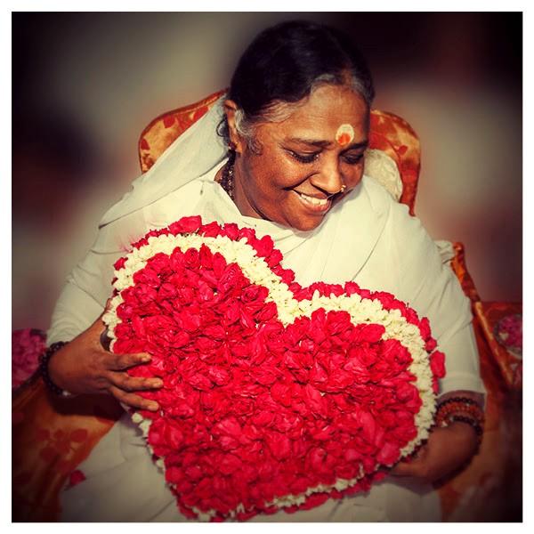 Amma hält ein Herz aus Blumen