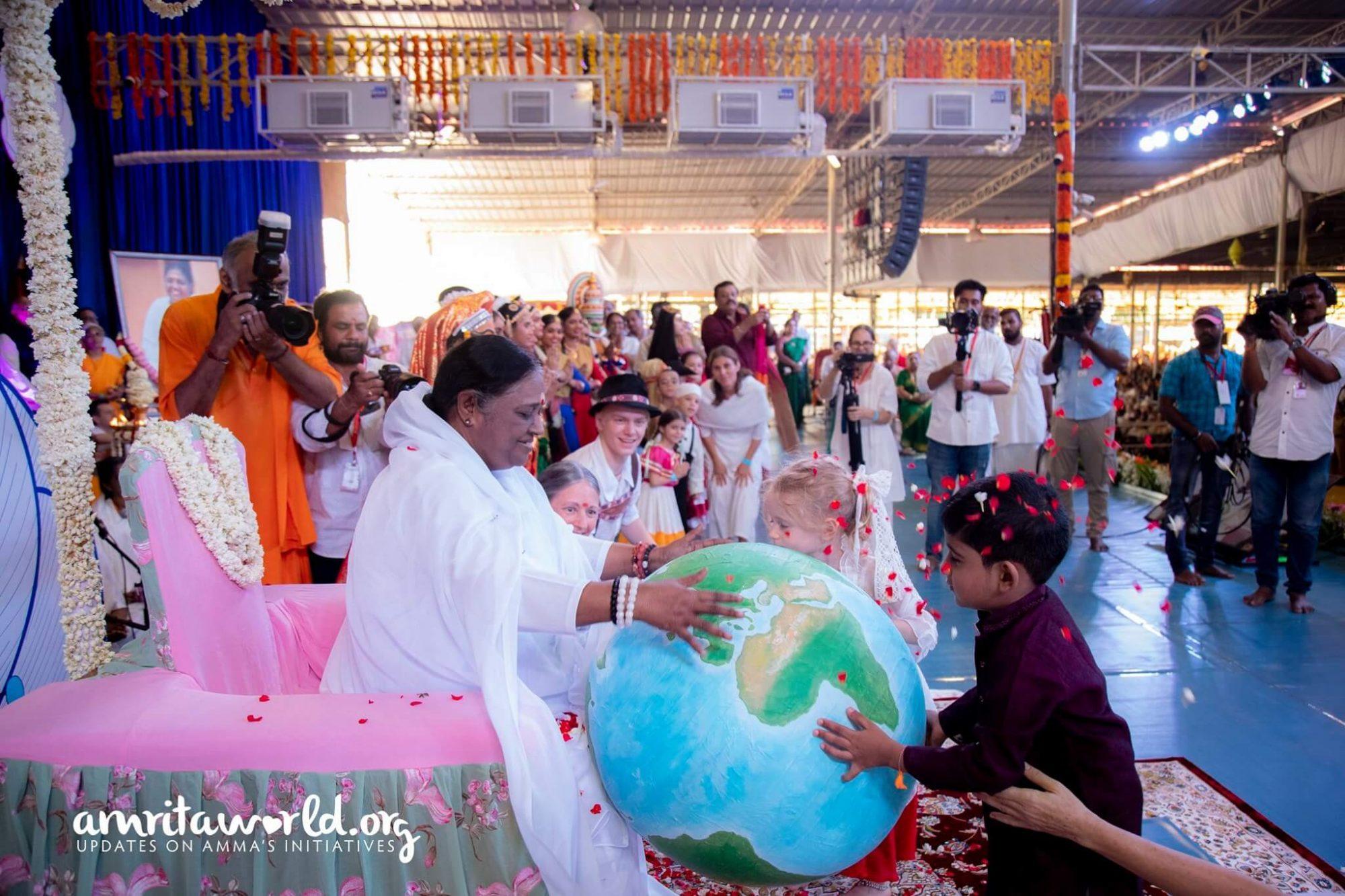 Kinder überreichen Amma einen Globus